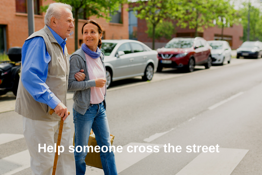 Senior and caregiver go walking outdoors and cross a street