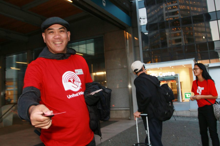 a volunteer hands out cards outside the skytrain station