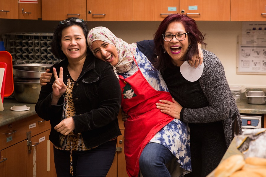 Three women stand together hugging each other and laughing.