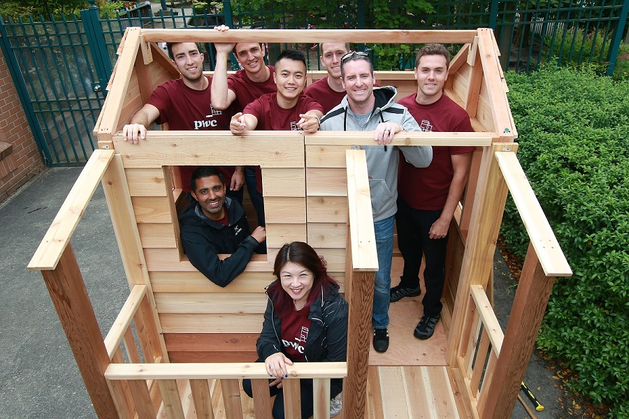 volunteers inside a playhouse they built