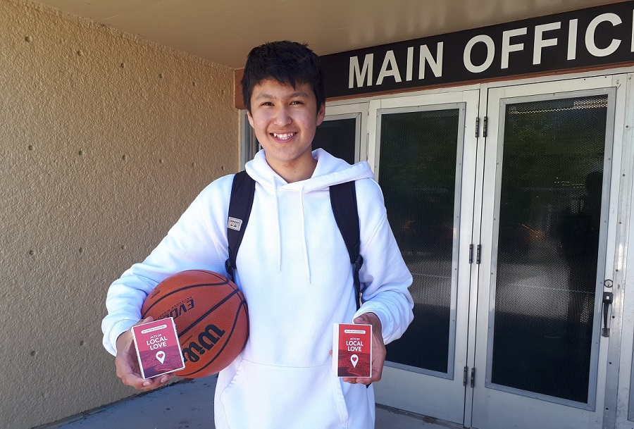 boy holding a basketball and cards