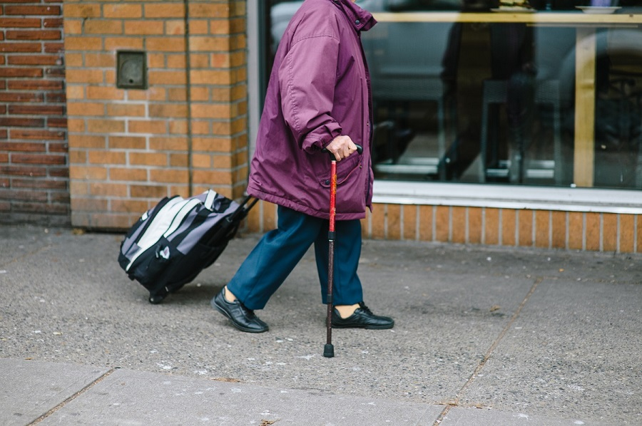 Senior walking with cane and bag