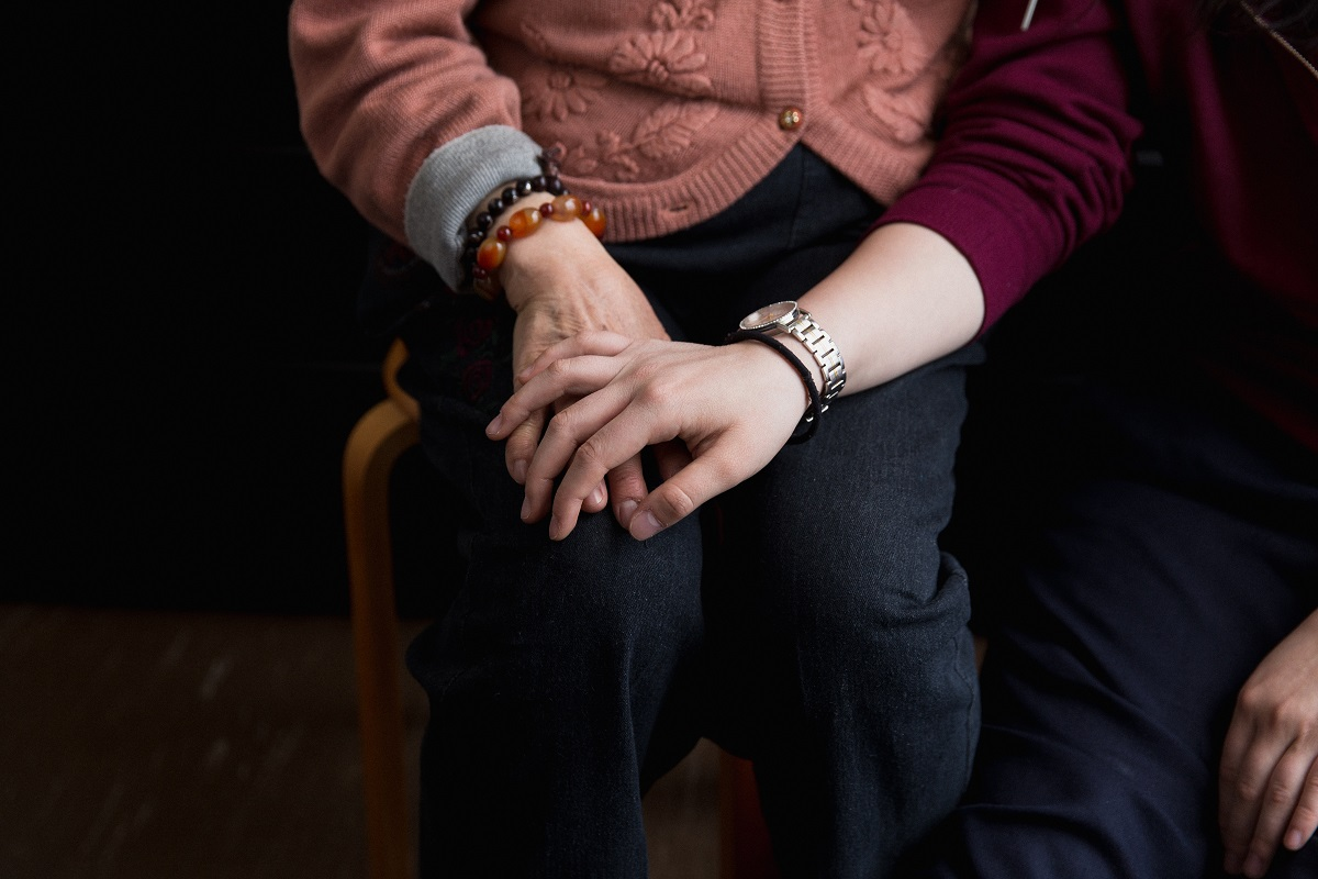 Two hands hold each other. One is from an older woman and the other is from a young woman.