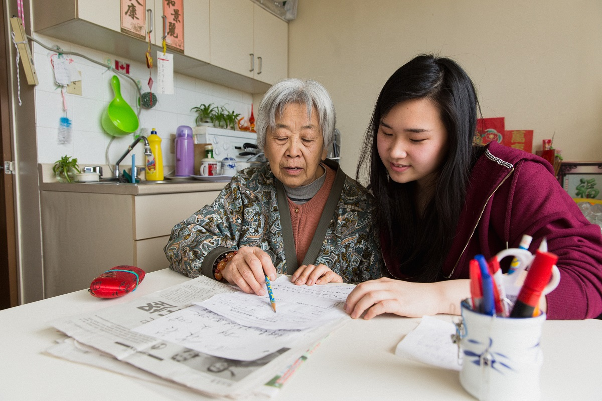 An older woman and a young woman sit at a table together, looking at a piece of paper.