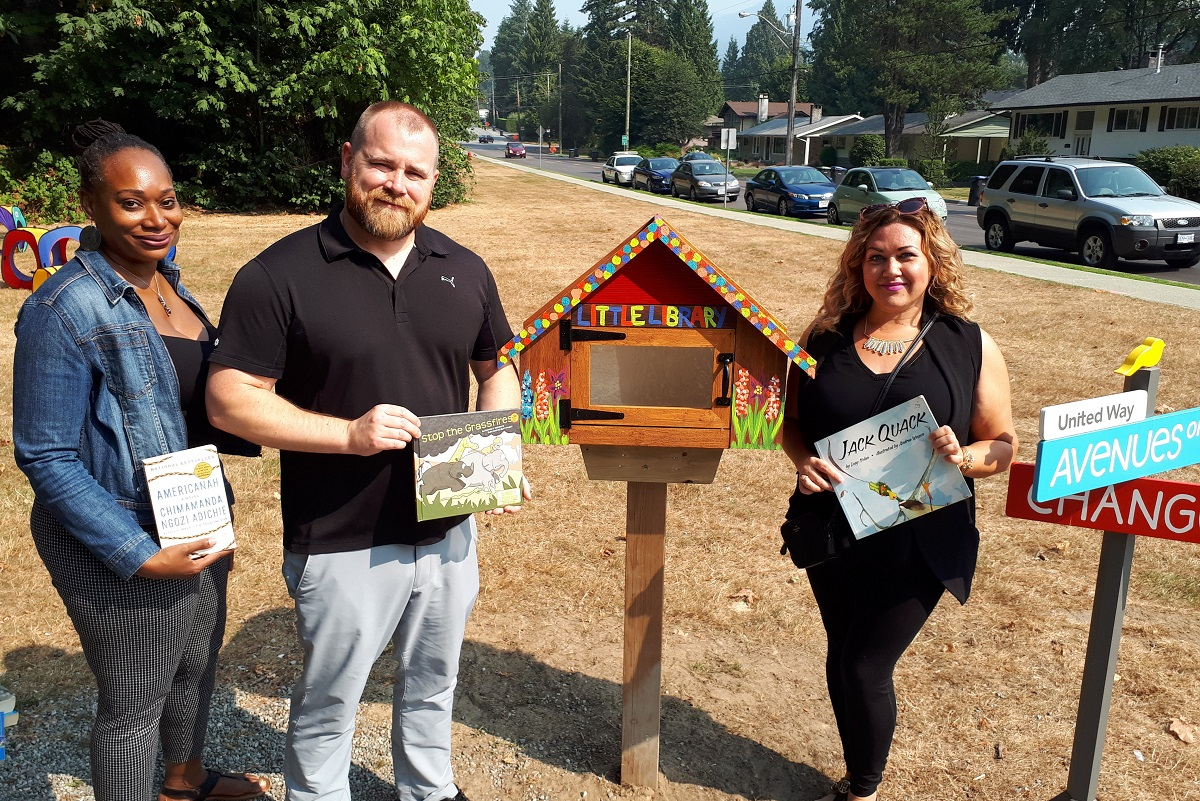 Three people stand in front of a little library in Port Coquitlam.