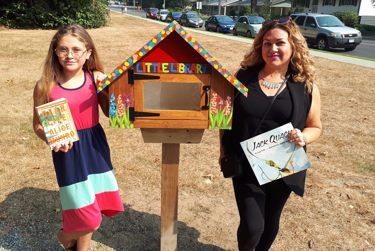 A mother and daughter stand in front of a little library.