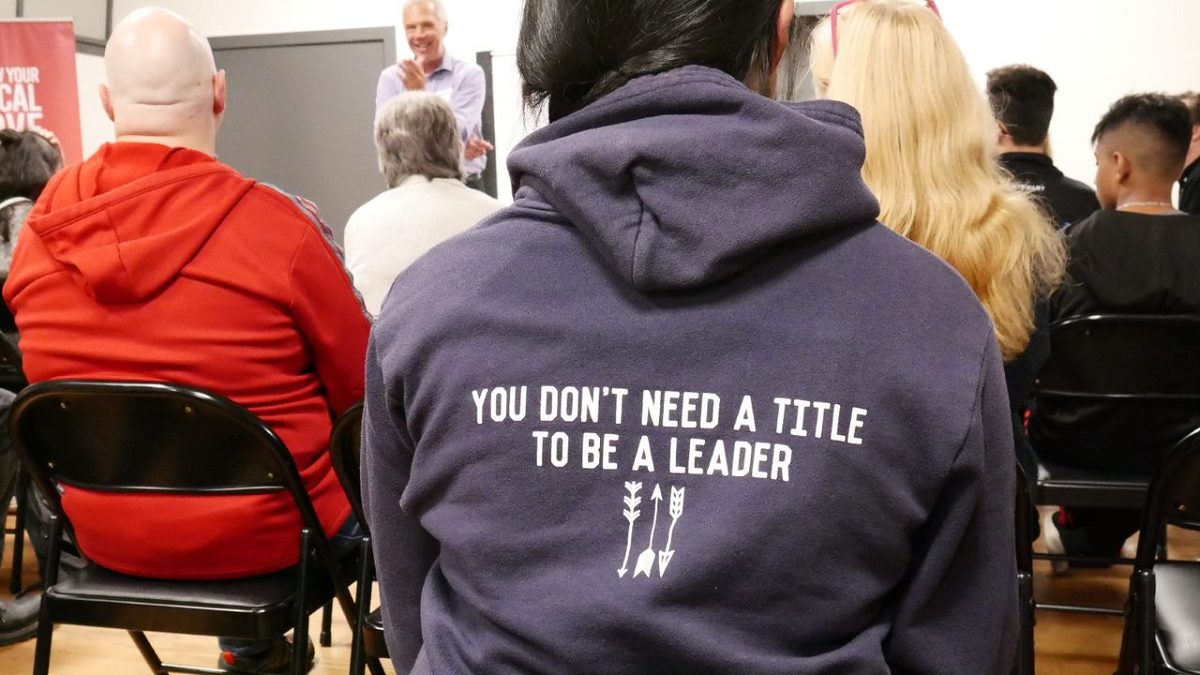 """A teenager sits wearing a purple hoodie with """"You don't need a title to be a leader"""" written on it."""