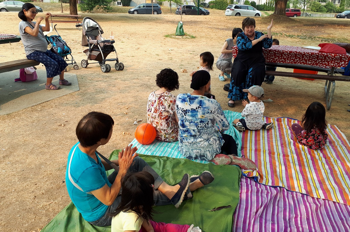 A group of parents and caretakers sit with children listening to a story in a park.