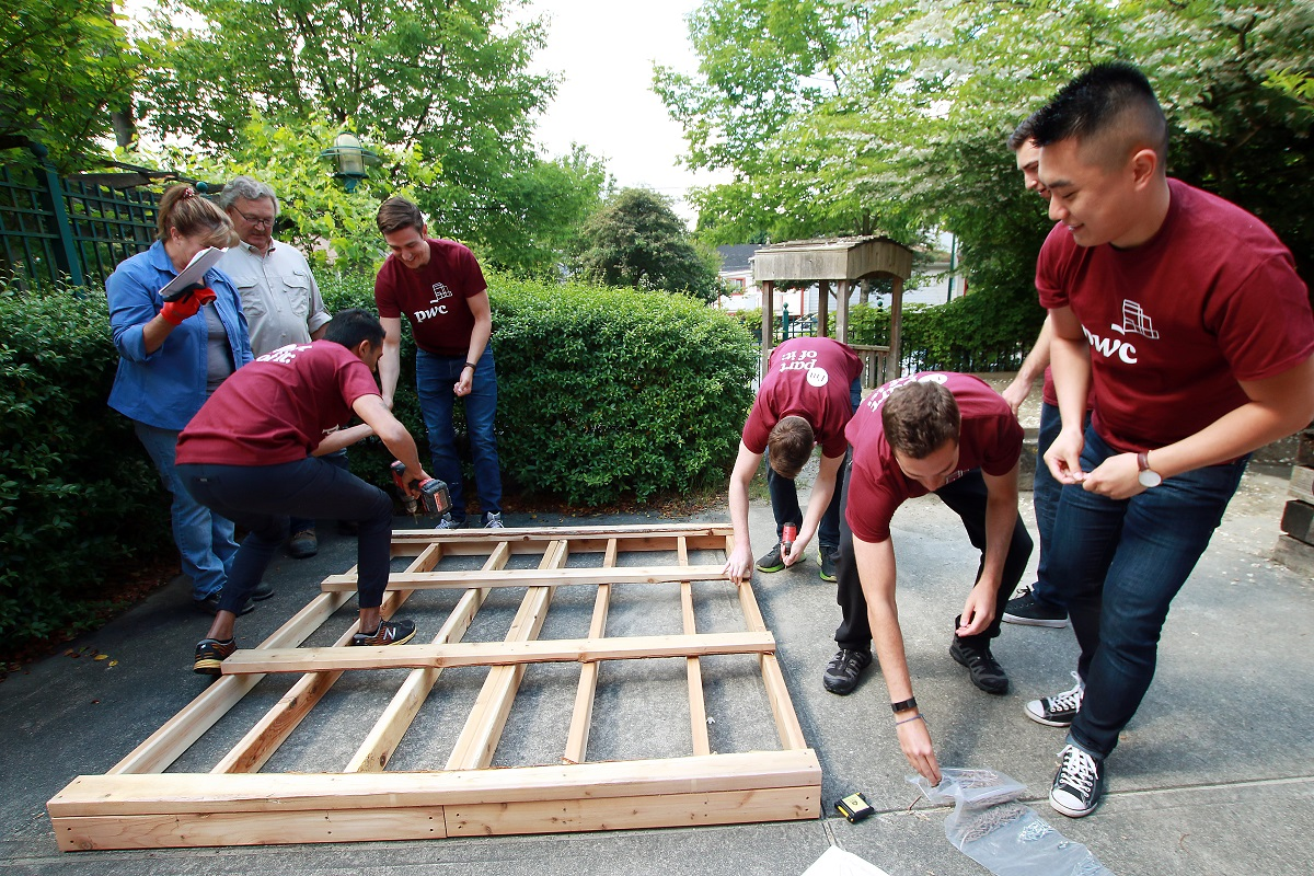 Men and women work together to nail together wooden planks.