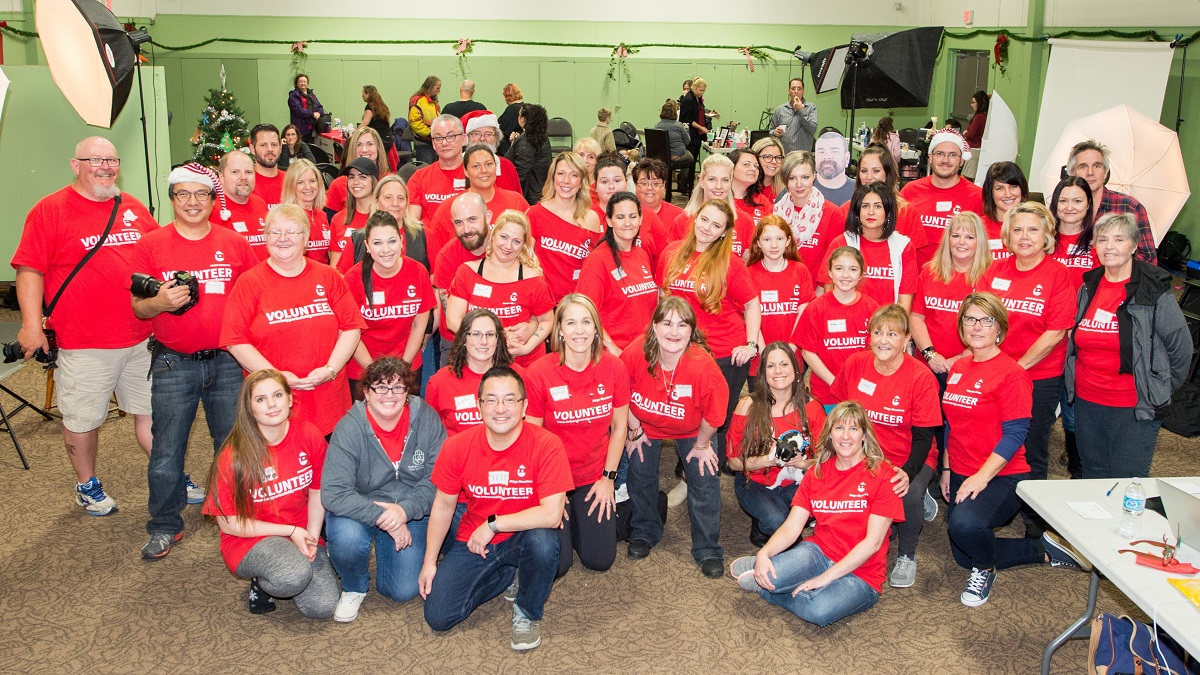 A group of people wearing red shirts smile at the camera.