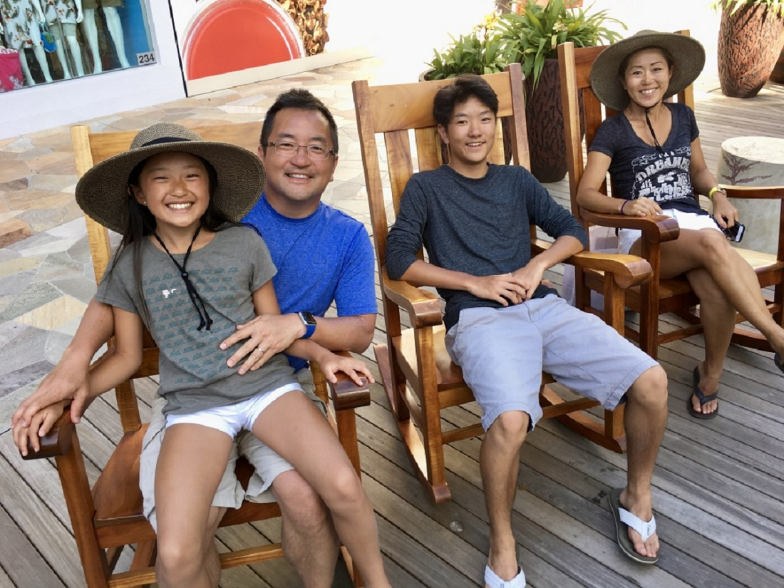 A smiling family sits on deck chairs.