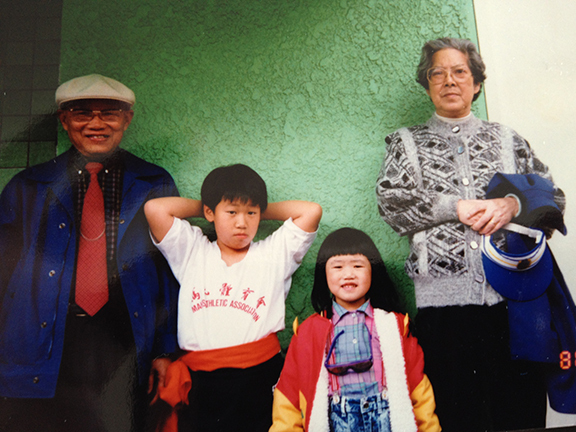 A family stands in front of a green wall.