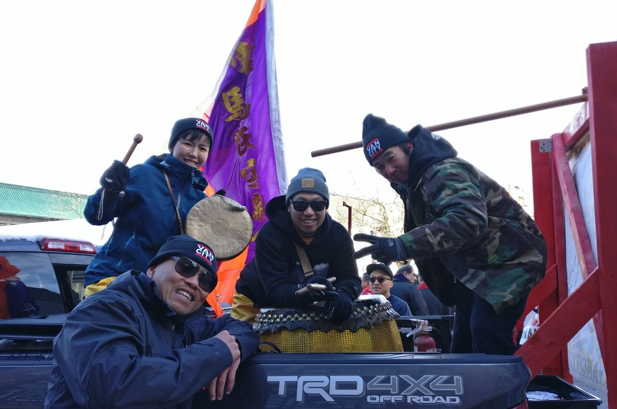 A group of people smile with their drums in the back of a truck.