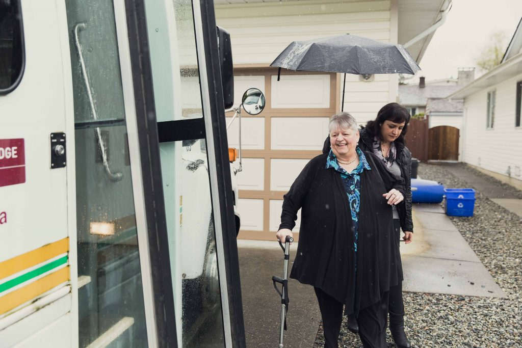senior angie gets help into a bus